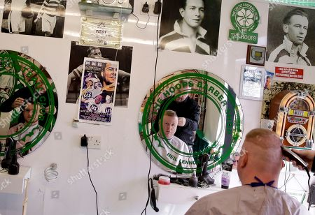 A man has his hair cut in Hoops barber shop surrounded by memorabilia of Celtic Football Cub on the Falls Road in Belfast, Northern Ireland, . The death last week of Martin McGuinness, the Irish Republican Army commander who led his underground paramilitary movement toward reconciliation with Britain, highlighted the progress that has been made in Northern Ireland, yet how far there is still to go