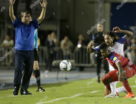 Panama's head coach Hernan Gomez, left, lightship arms in protest as Panama's Armando Cooper, red, fights fro the ball with United States' Jermaine Jones during a 2018 World Cup qualifying soccer match in Panama City