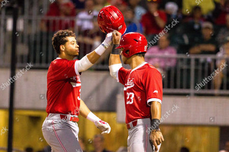 Stock Image of NC State infielder Joe Dunand (3) celebrates with catcher Jack Conley (23) after his home run in the NCAA Baseball matchup at BB&T Ballpark in Charlotte, NC