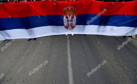 Supporters of presidential candidate Sasa Jankovic hold Serbian flag during a pre-election rally, in Belgrade, Serbia, . Sasa Jankovic and Vuk Jeremic, two main opposition candidates differ on many things, but they agree on one: the campaign ahead of Serbian presidential election is the dirtiest since the votes that kept former strongman Slobodan Milosevic in power in the 1990s