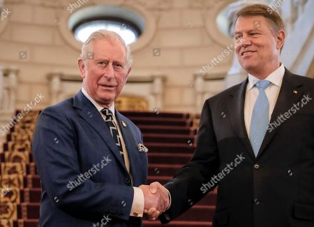 Britain's Prince Charles, left, shakes hands with Romanian President Klaus Ioannis at the Cotroceni Presidential Palace in Bucharest, Romania, . Britain's Prince Charles has arrived in Bucharest at the start of a nine-day tour to Romania, Italy and Austria that the British government hopes will reassure European Union nations that Britain remains a close ally despite its intention to quit the bloc
