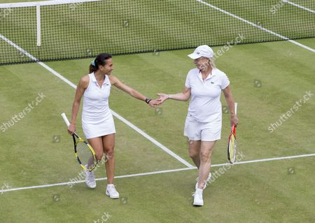 Martina Navratilova (USA) and Selima Sfar (TUN) high five during their Ladies' Invitational Doubles match with Helena Sukova (CZE) and Jana Novotna (CZE) The Championships 2016 at The All England Lawn Tennis Club.