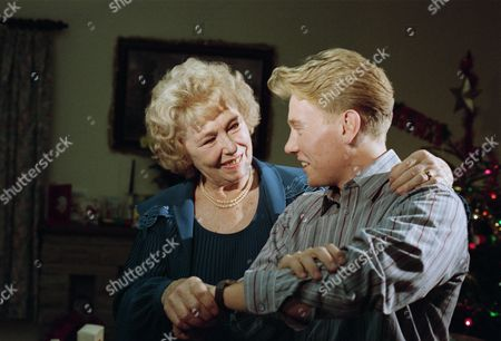 Stock Photo of Sheila Mercier (as Annie Kempinski) with Craig McKay (as Mark Hughes) as the Sugden family exchange gifts, as Annie gives Jacob's gold watch to Mark (Ep 1828 - 23rd December 1993)