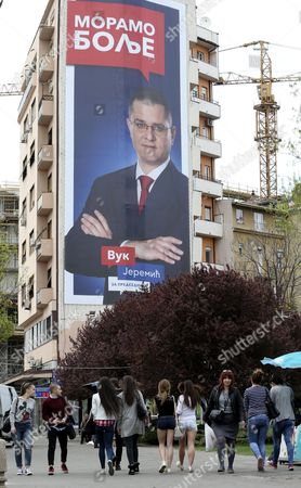 People pass by the billboard of candidate for the Serbian presidency, Vuk Jeremic, in Belgrade, Serbia, 30 March 2017. Serbian presidential elections will be held on 02 April 2017.