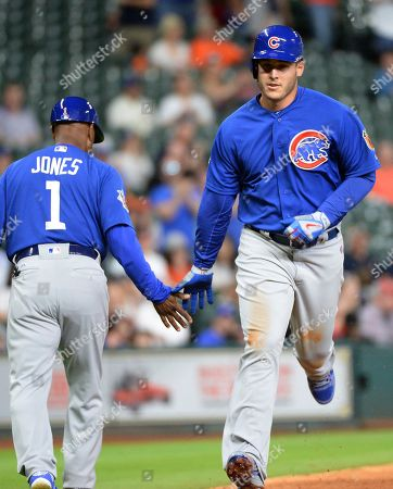 Chicago Cubs' Anthony Rizzo is congratulated by third base coach Gary Jones after a solo home run against the Houston Astros during the fifth inning of an exhibition baseball game, in Houston