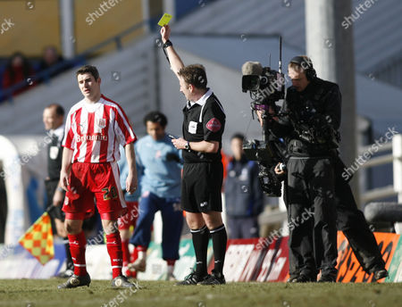 Andy Griffin of Stoke City is booked by Referee J Moss under the gaze of the television cameras.