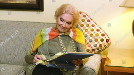 """Stock Picture of Suzanne Lloyd looks at unseen photographs in the """"Blue books"""" at her home in Los Angeles"""