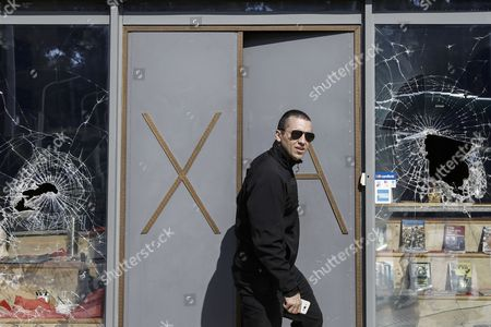 Spokesman of the far-right Golden Dawn party Ilias Kasidiaris leaves the damaged party's store, next to party's headquarters, following an attack, in Athens, Greece, 31 March 2017. Police are investigating an attack against the office branch of the extreme right Golden Dawn on Friday morning by unknown assailants. According to initial reports, the attackers smashed the office windows and threw paint.