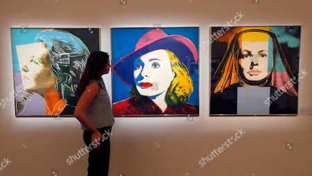 A Sotheby's employee looks towards a set of three screen prints by Andy Warhol called 'Ingrid Bergman: Herself, The Nun and With Hat' at Sotheby's auction rooms in London, . The prints are expected to realise 50,000-70,000 UK pounds (62,214- 87,099 US dollars) when they are auctioned in the 'Prints and Multiples' sale on April 4
