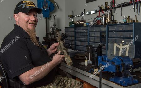 Stock Photo of Jamey Spears, an ammunition expert for Battle Rifle Co. poses with a gun part in Webster, Texas. Battle Rifle is now one of more than 10,000 gunmakers in the United States. President Donald Trump promised to revive manufacturing in the U.S., but one sector is poised to shrink under his watch: the gun industry. Fears of limits on guns led to a surge in demand during President Barack Obama's tenure and manufacturers leapt to keep up