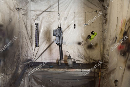 Parts from an AR-15 style rifle hang after being painted in a room at Battle Rifle Co. in Webster, Texas. Battle Rifle is now one of more than 10,000 gunmakers in the United States. President Donald Trump promised to revive manufacturing in the U.S., but one sector is poised to shrink under his watch: the gun industry. Fears of limits on guns led to a surge in demand during President Barack Obama's tenure and manufacturers leapt to keep up