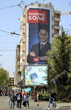 People walk near a billboard of candidate for the Serbian presidency, Vuk Jeremic, in Belgrade, Serbia, 01 April 2017. The Serbian Presidential election is scheduled to take place on 02 April 2017.