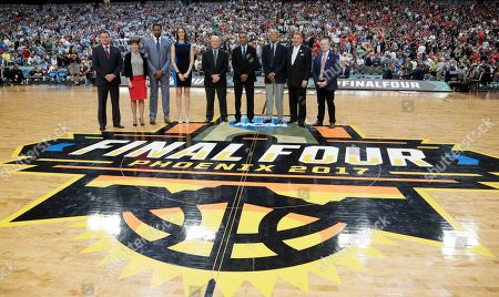 Basketball Hall of Fame members from left, Bill Self, Muffet McGraw, Tracy McGrady, Rebecca Lobo, Tom Jernstedt, Mannie Jackson and Robert Hughes stand with Jerry Colanego and John Doleva, president and CEO of the Hall of Fame, right, during halftime of the semifinal between Gonzaga and South Carolina in the Final Four NCAA college basketball tournament, in Glendale, Ariz