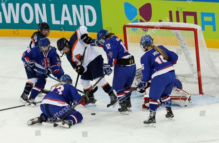Emily Even, Louise Adams, Clara Ashton Netherlands's Emily Even, center, fights for the puck with Britain's Louise Adams, second from right, and Clara Ashton, second from left, during their IIHF Ice Hockey Women's World Championship Division II Group A game in Gangneung, South Korea