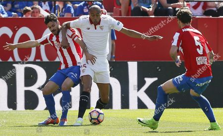 Sevilla FC's French midfielder Steven N'Zonzi (C) vies for the ball with Roberto Canella (L) and Fernando Amorebieta of Sporting Gijon during a Spanish Primera Division League soccer match between Sevilla FC and Sporting Gijon at the Sanchez Pizjuan stadium in Seville, southern Spain, 02 April 2017.
