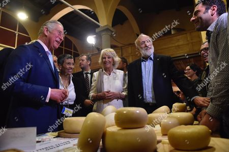 Britain's Prince Charles (L), Camilla Duchess of Cornwall (C) and founder and president of the gastronomic movement Slow Food, Carlo Petrini (C-R) look at cheese wheels as they visit the Teatro del Sale in Florence, Italy