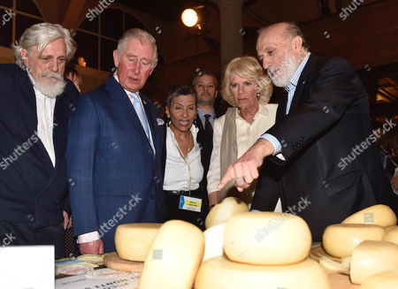 Britain's Prince Charles (2-L), Camilla Duchess of Cornwall (2-R) and founder and president of the gastronomic movement Slow Food, Carlo Petrini (R) look at cheese wheels as they visit the Teatro del Sale in Florence, Italy