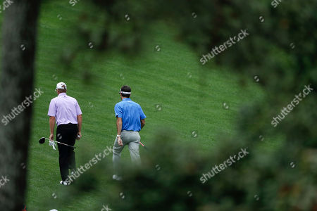Bubba Watson, right, and Steven Stricker walk down the 11th hole during a practice round for the Masters golf tournament, in Augusta, Ga