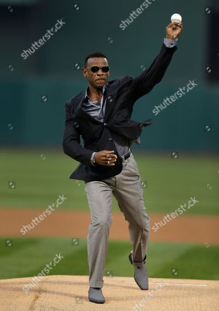 Former Oakland Athletic and Baseball Hall of Fame inductee Rickey Henderson throws out the ceremonial first pitch on the newly dedicated Rickey Henderson field prior to the baseball game against the Los Angeles Angels, in Oakland, Calif