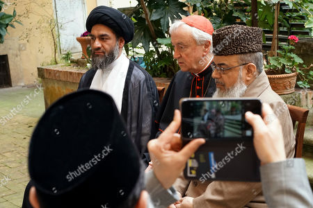 Shaykh Ibrahim Mogra takes pictures of Cardinal Vincent Nichols, Archbishop of Westminster, center, Ali Raza Rizvi, left, and Muhammad Shahid Raza, chairman of the British Muslim Forum, as they answer questions during an interview with The Associated Press, at Rome's English College, . Pope Francis is meeting with four British imams two weeks after the Westminster attack, part of his effort to give prominence and a platform to Muslim leaders who renounce using religion to justify violence