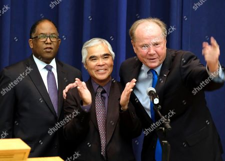 """Stock Image of Chairman of the Los Angeles County Board of Supervisors Mark Ridley-Thomas, left, with former Los Angeles City Councilman Tom LaBonge, right, presents Associated Press photographer Nick Ut with a proclamation of April 4, 2017 as """"Nick Ut Day"""" in the County of Los Angeles on . The presentation of scroll to Pulitzer Prize-winning photographer Ut in recognition of his retirement after 51 years at the Associated Press"""