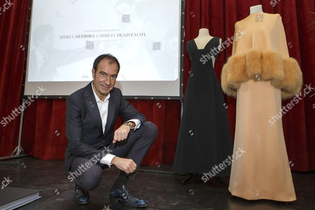 """Eloy Martinez de la Pera Celada, curator of the exhibition, poses next to two dresses of the Countess von Galen created by Hubert de Givenchy, during the presentation of the exhibition """"Audrey Hepburn & Hubert de Givenchy: une elegante amitie"""", in Morges, Switzerland, 05 April 2017. The exhibition """"Audrey Hepburn & Hubert de Givenchy: une elegante amitie"""" (English: """"Audrey Hepburn & Hubert Givenchy: """"An elegant friendship"""") will take place from May 20 to September 17, 2017, at the Expo Fondation Bolle in Morges."""