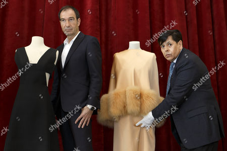 """Stock Photo of Antonio Villaverde, right, curator of the Musee Suisse de la Mode, removes one of the two dresses of the Countess von Galen created by Hubert de Givenchy next to Eloy Martinez de la Pera Celada, left, curator of the exhibition, during the presentation of the exhibition """"Audrey Hepburn & Hubert de Givenchy: une elegante amitie"""", in Morges, Switzerland, 05 April 2017. The exhibition """"Audrey Hepburn & Hubert de Givenchy: une elegante amitie"""" (English: """"Audrey Hepburn & Hubert Givenchy: """"An elegant friendship"""") will take place from May 20 to September 17, 2017, at the Expo Fondation Bolle in Morges."""