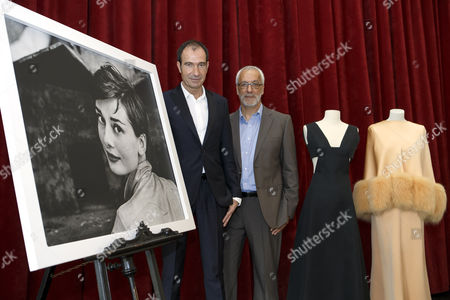 """Eloy Martinez de la Pera Celada, left, curator of the exhibition, and Salvatore Gervasi, director of Expo Fondation Bolle, right, pose next to a portrait of Audrey Hepburn and two dresses of the Countess von Galen created by Hubert de Givenchy, during the presentation of the exhibition """"Audrey Hepburn & Hubert de Givenchy: une elegante amitie"""", in Morges, Switzerland, 05 April 2017. The exhibition """"Audrey Hepburn & Hubert de Givenchy: une elegante amitie"""" (English: """"Audrey Hepburn & Hubert Givenchy: """"An elegant friendship"""") will take place from May 20 to September 17, 2017, at the Expo Fondation Bolle in Morges."""