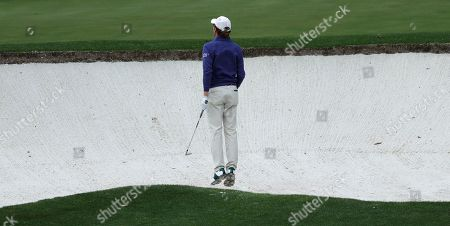 Roberto Castro leaps to see his bunker shot on the fourth hole during the first round for the Masters golf tournament, in Augusta, Ga