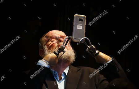 A man with prosthetic hands operates a cellphone as he attends the memorial serice for Ahmed Kathrada in Cape Town, South Africa, 06 April 2017. Kathrada, an anti-apartheid struggle icon and close friend of the late former South African President, Nelson Mandela died on 28 March.  Former Finance Minister Pravin Gordhan was given a standing ovation as various speakers at the service slated President Zuma amidst a growing backlash against his recent government reshuffle and axing of the finance minister.
