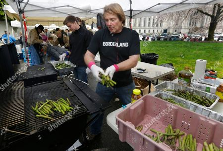 Gary Larsen, center, chairman of the Washington Asparagus Commission, grills freshly harvested asparagus alongside his son Tanner, left, outside the Legislative Building at the Capitol in Olympia, Wash. The group decided to serve up Washington-grown asparagus to Capitol visitors alongside members of the Washington Cattlemen's Association, who were serving sliced beef tri-tip roasts as part of their annual Beef Day