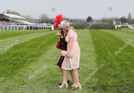 Two Ladies cross the course in fron of the Chair  during Ladies Day of The Grand National Meeting at Aintree  on 7th April 2017 Picture Luke Williams/BPI