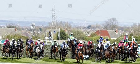 Stock Photo of LIAM TREADWELL takes a fall with BRIGHT NEW DAWN at the first fence in The Randox Health Topham Handicap Chase won by ULTRAGOLD Aintree