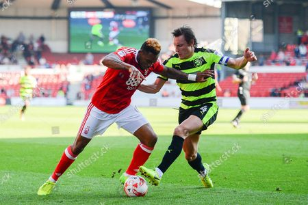 Nottingham Forest forward Britt Assombalonga (9) battles with Huddersfield Town midfielder Dean Whitehead (4) during the EFL Sky Bet Championship match between Nottingham Forest and Huddersfield Town at the City Ground, Nottingham