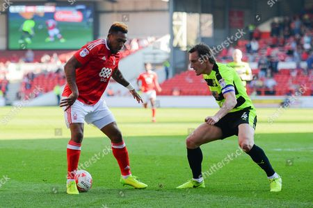 Nottingham Forest forward Britt Assombalonga (9) with Huddersfield Town midfielder Dean Whitehead (4) closing in during the EFL Sky Bet Championship match between Nottingham Forest and Huddersfield Town at the City Ground, Nottingham