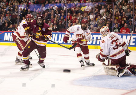 Minnesota Duluth forward Adam Johnson (7) and Denver defenseman Will Butcher (4) skate for the puck during NCAA Hockey Frozen Four Championship game action between the Minnesota-Duluth Bulldogs and the Denver Pioneers at United Center in Chicago, Illinois. Denver defeated Minnesota-Duluth 3-2