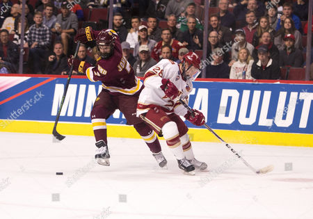 Minnesota Duluth forward Adam Johnson (7) skates with the puck as Denver defenseman Adam Plant (28) defends during NCAA Hockey Frozen Four Championship game action between the Minnesota-Duluth Bulldogs and the Denver Pioneers at United Center in Chicago, Illinois. Denver defeated Minnesota-Duluth 3-2