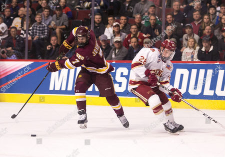 Minnesota Duluth forward Adam Johnson (7) skates with the puck as Denver defenseman Adam Plant (28) defends during NCAA Hockey Frozen Four Championship game action between the Minnesota-Duluth Bulldogs and the Denver Pioneers at United Center in Chicago, Illinois