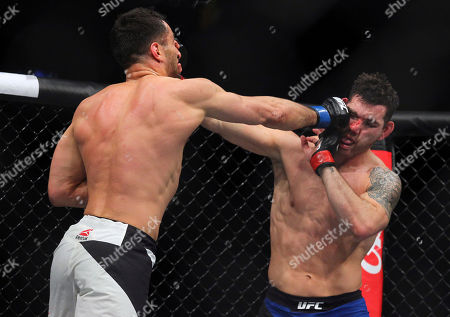 Gerard Mousasi, left, hits Chris Weidman during a middleweight mixed martial arts bout at UFC 210, in Buffalo, N.Y