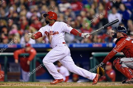 Stock Picture of Philadelphia Phillies' Howie Kendrick hits a three-run triple off Washington Nationals starting pitcher Jeremy Guthrie during the first inning of a baseball game, in Philadelphia. The Phillies won 17-3