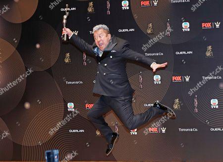 "Hong Kong actor Eric Tsang poses after winning the Best Supporting Actor award for his movie ""Mad World"" during the Hong Kong Film Awards in Hong Kong"