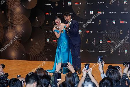 Stock Image of Kara Wai, Gordon Lam Hong Kong actress Kara Wai, left and actor Gordon Lam pose after winning the Best Actress and Best Actor awards during the Hong Kong Film Awards in Hong Kong