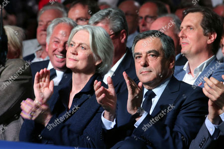 Conservative French presidential candidate Francois Fillon, right, and his wife Penelope applaud during a campaign meeting in Paris, France, . The two-round presidential election is set for April 23 and May 7