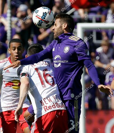 Sacha Kljestan, Antonio Nocerino Orlando City's Antonio Nocerino, right, goes up over New York Red Bulls's Sacha Kljestan (16) to head the ball away during the first half of an MLS soccer game, in Orlando, Fla
