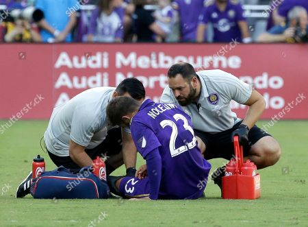 Team trainers check on Orlando City's Antonio Nocerino (23) after he was injured during the first half of an MLS soccer game against the New York Red Bulls, in Orlando, Fla