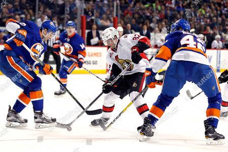 Ottawa Senators center Colin White (82) looks to control the puck between New York Islanders defenseman Adam Pelech and Islanders defenseman Scott Mayfield (42) in the third period of an NHL hockey game, in New York. The Islanders won 4-2