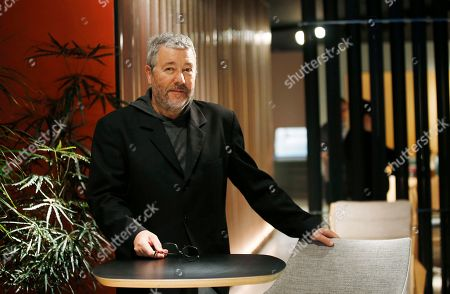 On, designer Philippe Starck poses for a photographer after an interview with the Associated Press, at the Cassina space, part of the Design Fair exhibition in Milan, Italy
