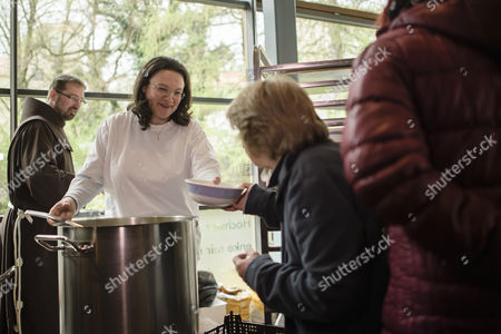 Stock Image of German Minister of Work and Social Issues Andrea Nahles (2-L) distributes soup to people in need at the soup kitchen of a Franciscan Order while Brother Andreas (L) stands next to her in Berlin, Germany, 11 April 2017.
