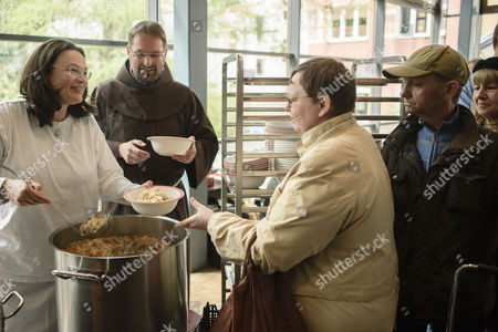 Stock Image of German Minister of Work and Social Issues Andrea Nahles (L) distributes soup to people in need at the soup kitchen of a Franciscan Order while Brother Andreas (2-L) stands next to her in Berlin, Germany, 11 April 2017.