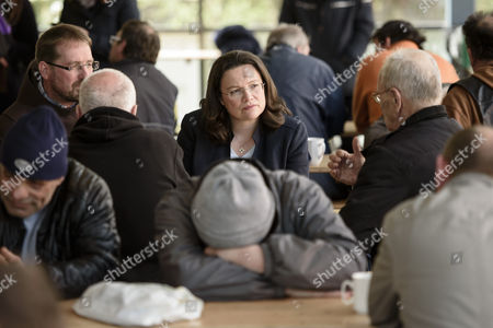 Germany's Minister of Labor and Social Affairs Andrea Nahles (C) talks to people in need at the soup kitchen of a Franciscan Order while Brother Andreas (L) sits next to her in Berlin, Germany, 11 April 2017.